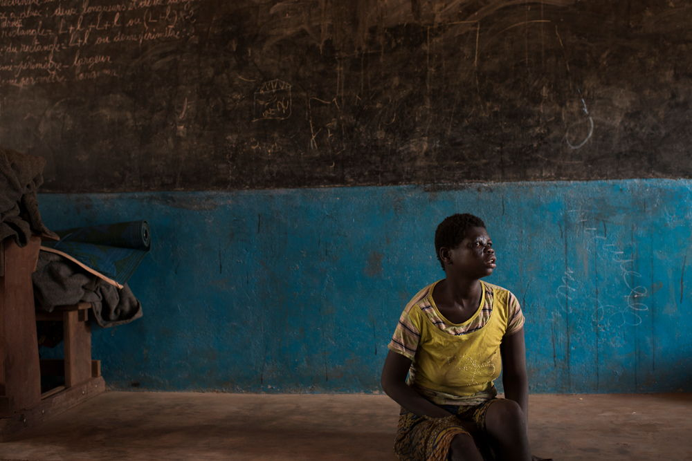 Catherine, 16, fled her village with her parents and her fourteen brothers and sisters after it was burned. They found shelter in the village of Ngoubi's school, 18km from Bria. Photograpaher: Colin Delfosse