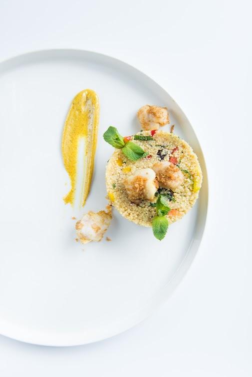 Jans café - quinoa-couscous salade met crispy roggewangetjes, met gemengde paprika, rozijnen en munt en een currydressing.