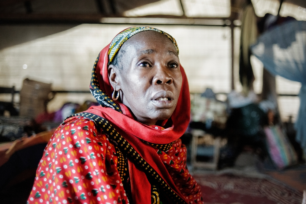 """MSF159643<br/>Portrait of 45 year old Alima at the at a camp for displaced persons at the Central Mosque in Bangui.<br/><br/>Alima and her family lived at the Miskin market in Bangui before the violence. One day an armed group surrounded the neighbourhood and killed people. After this, she fled with her family (4 boys, 3 girls and her little brother) to find safety at the Central Mosque of Bangui in PK5. After having stayed in the camp for a few days, her little brother wanted to return to their home to get some papers that he had not been able to take during their escape. When he arrived back home he was killed by a group of armed men. &quot;My little brother said: I am not a Seleka! But the attackers said he was a Muslim, which was enough to kill him"""". <br/><br/>Alima has never been able to retrieve the body of her little brother. Alima now lives in the Central Mosque in difficult conditions. She says she lost one of her sons who became sick due to the living conditions in the camp. Despite receiving treatment by the Red Cross. Alima is trying to cope by relying on the help of other people living with her in the camp, as she and her husband are unemployed. """"We were born here, our parents and grandparents too... and now we are treated as strangers&quot;. Last week, one of Alima's sons won a football tournament. The trophy is proudly displayed in their shelter."""