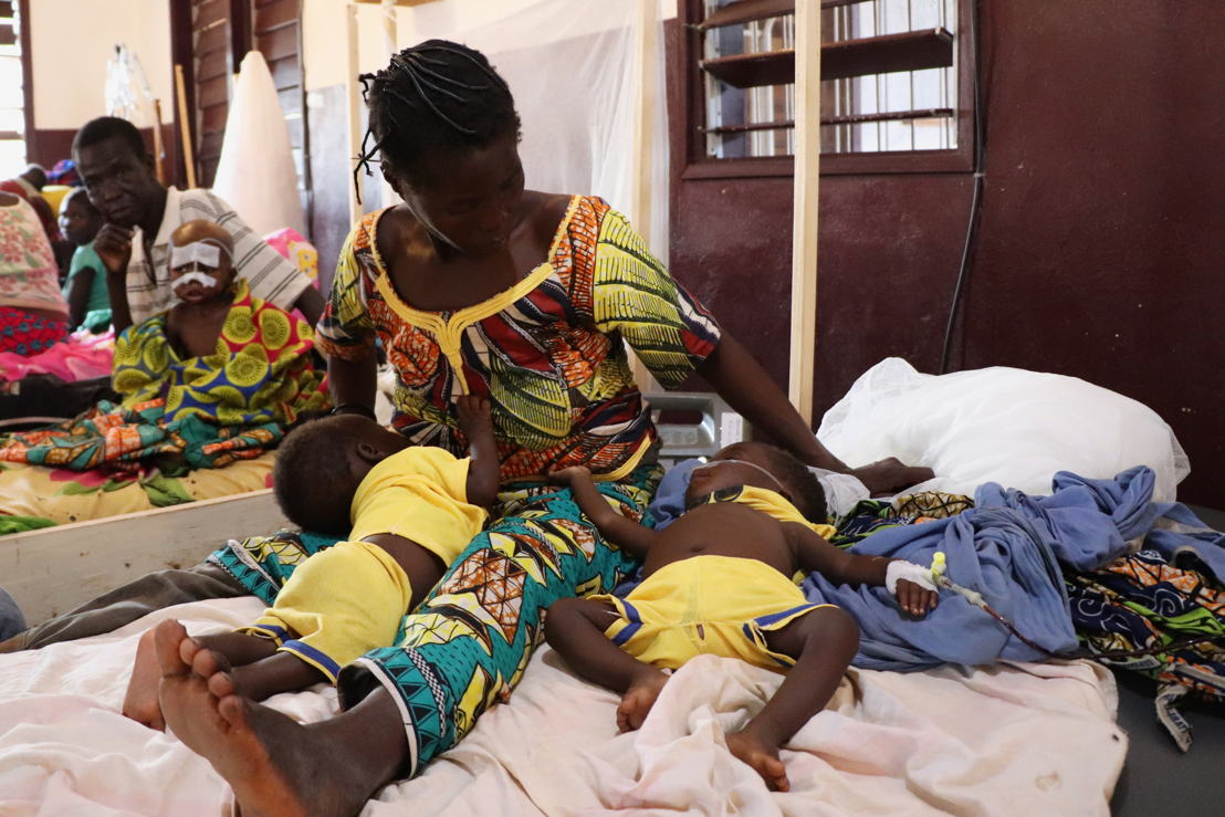 """Six-month-old twins Dieu Merci and Dieu Bénit asleep in the Bossangoa hospital intensive care unit. Germaine Voter, their mother, brought them to a health centre in Boguila when she noticed they both had a fever. There, they were diagnosed with malaria and sent directly to Bossangoa. """"It wasn't a surprise to me,"""" says Germaine. """"I knew what the symptoms were. They were shivering, but their bodies were warmer than normal. I just wish I would have noticed it sooner."""" Germaine left her other children at home to seek treatment for her sons. She doesn't know how long they will stay at the hospital. Photographer: Elisa Fourt"""