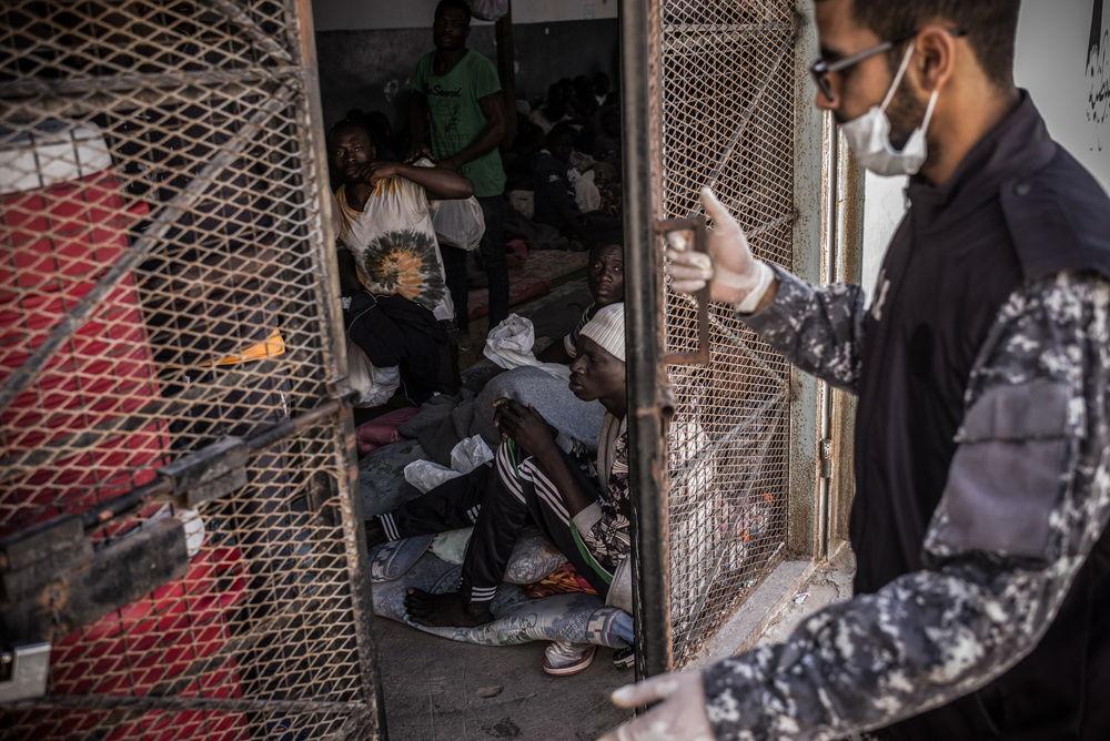 Un guarda cierra una puerta de una celda del centro de detención de Abu Salim, en Trípoli, en una imagen de 2017. © Guillaume Binet