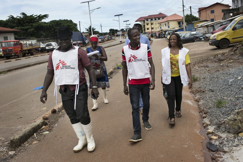 Health Promotion (HP) teams walk down the street of Yattaya Fossidé neighbourhood while conducting activities against the sigmatisation of Ebola survivors with the local population in Conakry. <br/><br/>(from left to right: Fodé Soumah, Camara Djenab, Cécé Dominique Delamou and Angeline Teinguiano). Photographer: Albert Masias