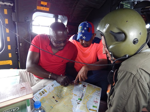 Grenada's Ambassador to the OECS H.E Dr. Patrick Antoine discusses food drop logistics mid flight on the way to Dominica. Photo credit: Janeka Simon