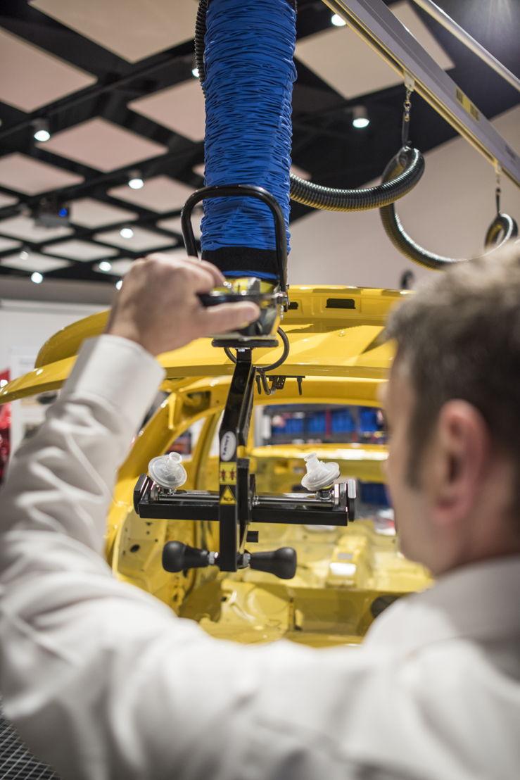 Medewerker demonstreert het nieuwe werktuig, waarmee de motorkap en het kofferdeksel moeiteloos kan openen, zodat de rug gespaard blijft. Het werktuig werd in Brussel ontwikkeld.
