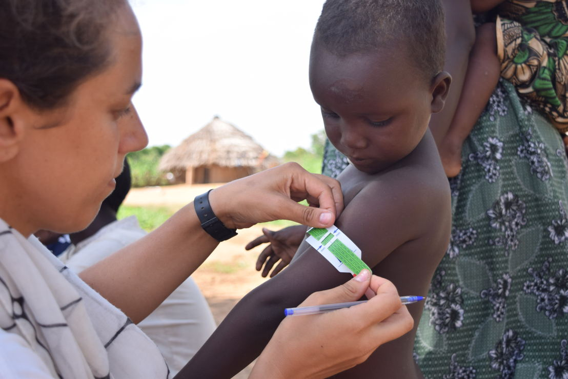"""Suzanne Moja, 36, from Madrid, Spain is an epidemiologist. She measures the middle upper arm circumference (MUAC) of a child as part of a survey to determine the impact of MSF&#039;s work to tackle malnutrition in the area.<br/>Around three times a year the team of epidemiologists and researchers travel to villages across Bokoro to survey 800 families and their children to understand the impact MSF's work is having. <br/>After finding a family who need to be surveyed, Suzanne and the team get to work. """"We informed the family of what we're doing and always ask their consent. Then we ask them some questions such as have they been to an MSF project, did they receive soap, plumpy'doz, mosquito nets and try to understand what they do with them."""" This family had tried to visit a nearby MSF clinic, but their children were over five years and so too old to be eligible for the malnutrition programme. Photographer: Charlotte Morris"""