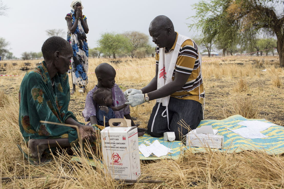 Outdoors support clinics, Thaker. Leer, South Sudan. Medecins Sans Frontieres (MSF) Community Health Promoter, Gatbel*, tests a child for malaria at an outdoor support clinic in Thaker, Leer County, South Sudan, March 18, 2017. ADDITIONAL INFORMATION / SHOTLIST:Three years after the beginning of the conflict, Leer and Mayendit counties are greatly affected by the ongoing violence and the longstanding clashes between governmental and opposition forces. Civilians are on the first line of the conflict and the ongoing violence has a very clear impact on the ability for the population to access basic and secondary medical care and other basic services. The population has been locally displaced multiple times; and many people had fled the area completely.<br/><br/>In July, following clashes in Leer County, the population again had to flee and Medecins Sans Frontieres (MSF) had to evacuate international teams from both Leer and Thonyor. In September MSF set up a decentralised basic healthcare programme to continue to reach the population and provide them with primary healthcare in their villages. Through a network of community health workers, community health promoters, and women health promoters, who live as part of the affected population, MSF teams have been able to continue to provide healthcare. These community health workers are trained in treating the most common morbidities, such as respiratory tract infections, malaria, water-borne diseases, etc. They stay with the community and are able to move with the communities if the population need to move, thus continuing to provide healthcare. MSF resupplies them with medical supplies and provides ongoing supervision and training through supporting international teams. Photographer: Siegfried Modola
