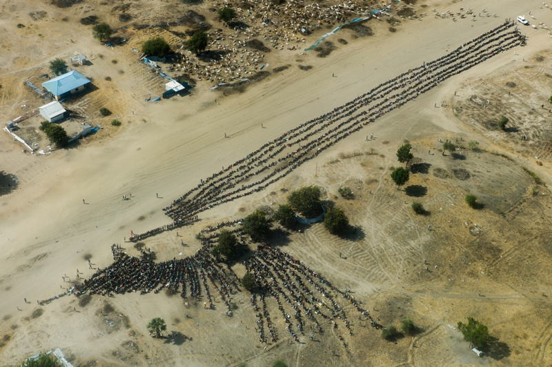 Lines of displaced people wait for an aid distribution in the otherwise empty and destroyed town of Leer, Unity state. Many thousands of people fled fighting in the area, seeking safety in the surrounding bush and swamplands or in the UN compound. Photographer: Dominic Nahr