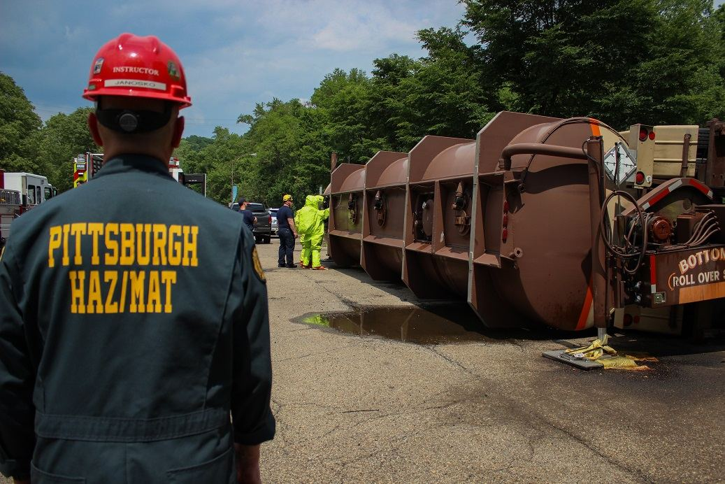 Crews from the Pittsburgh Bureau of Fire work during an exercise simulating an overturned tanker containing hazardous materials. The bureau teamed with Duquesne Light, which provided the hydraulic equipment to overturn the vessel. (Nick Ruffolo)