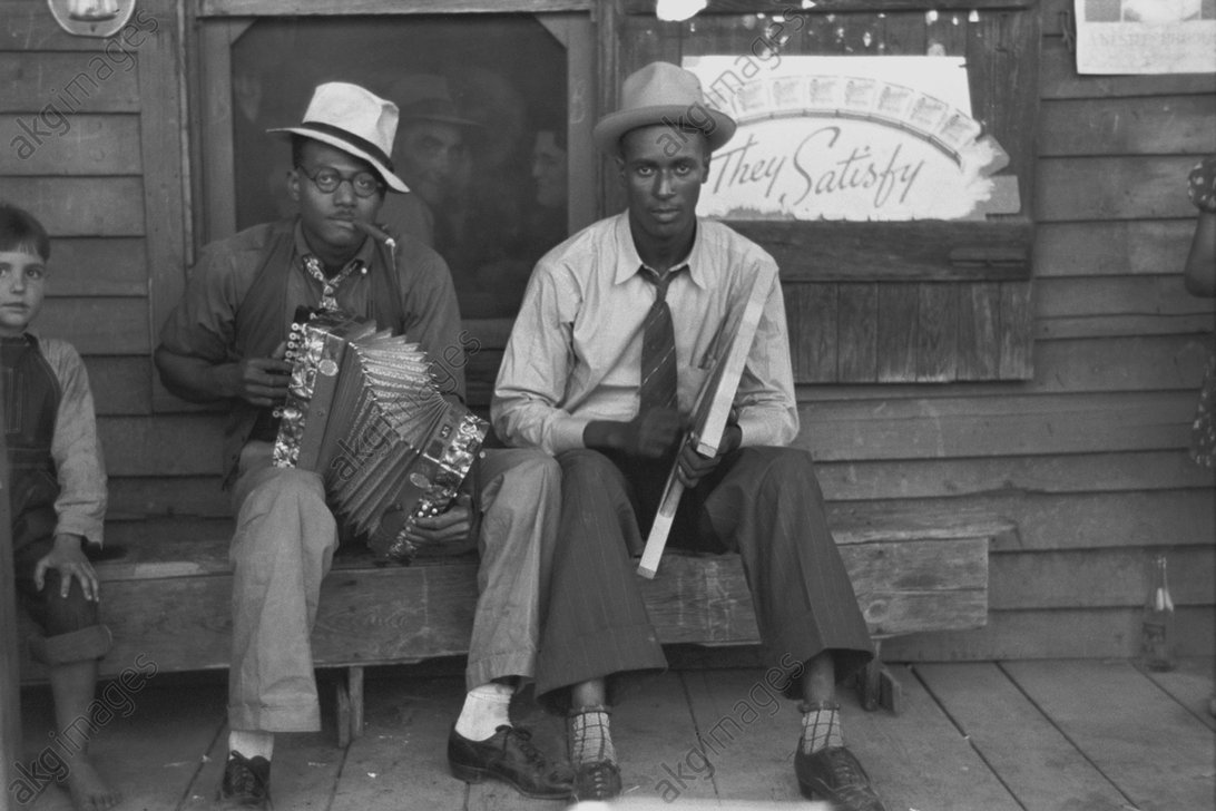 Two street musicians playing accordion and washboard in front of a shop near New Iberia, Louisiana. Photo, 1938<br/>AKG1772907