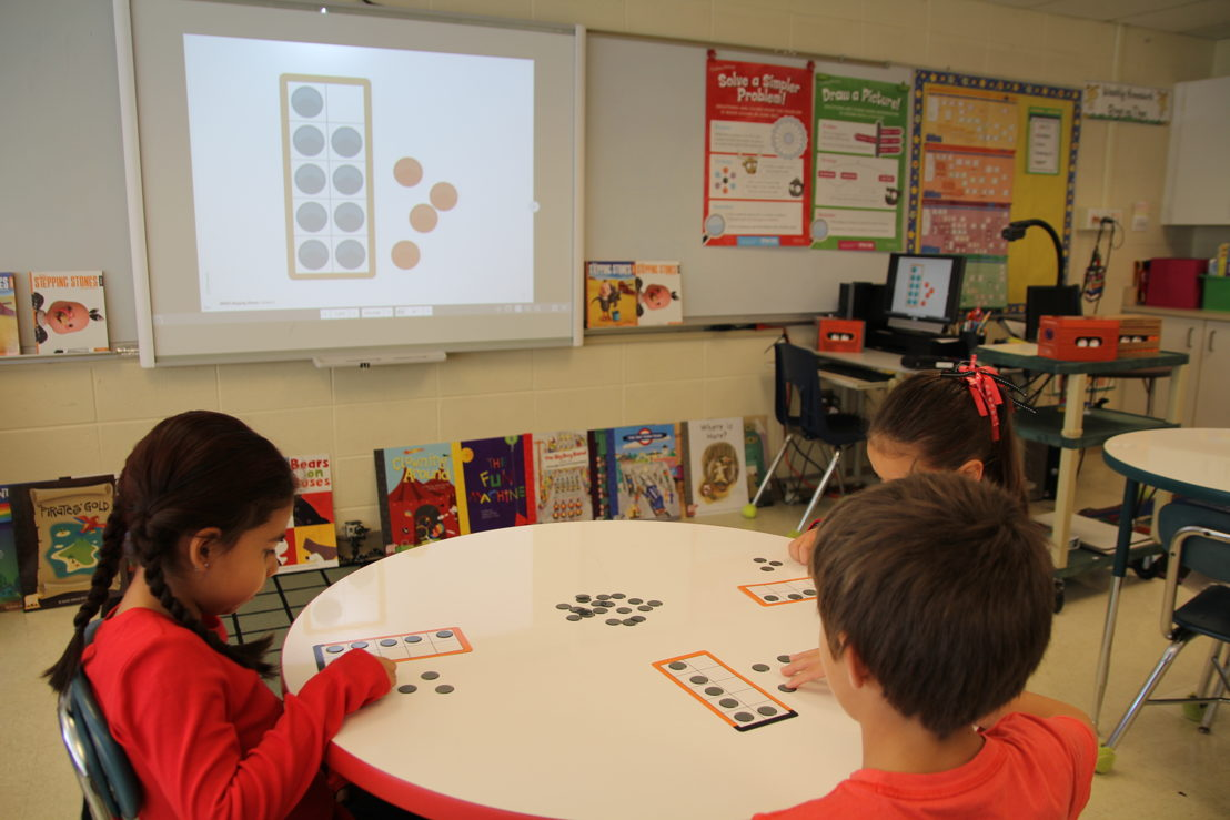 Students mimic what's on screen with hands-on counters