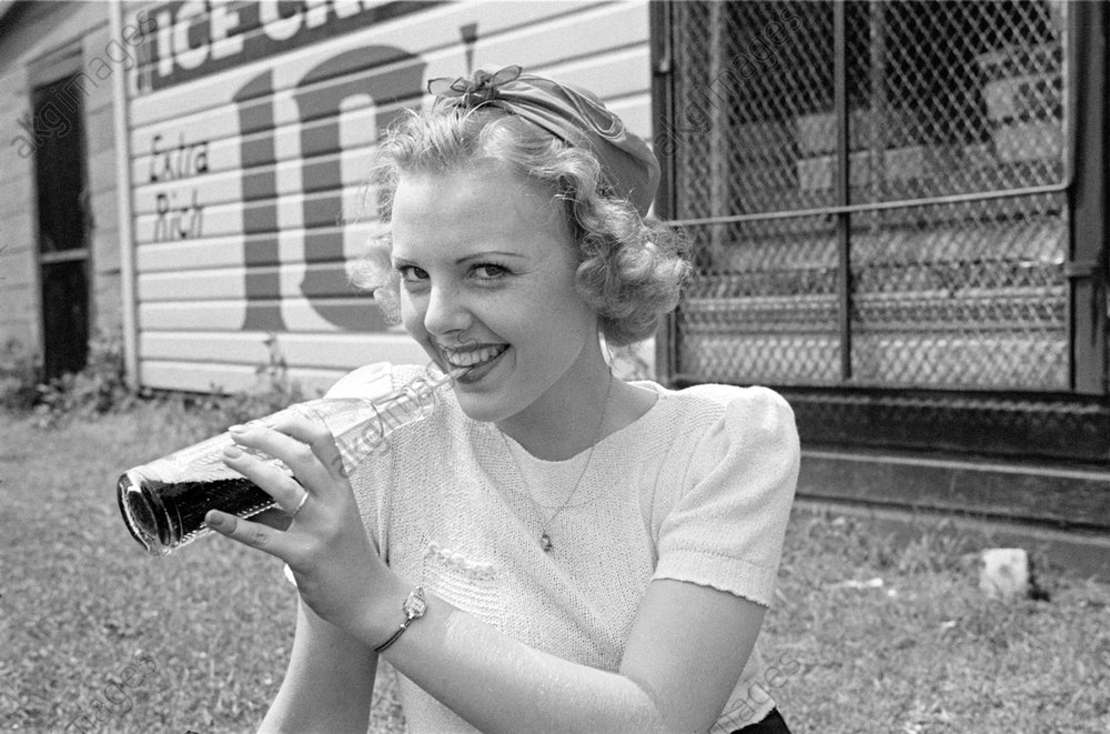 Barbara Bradford Mann in front of a sign reading 'Ice Cream – Extra Rich 10 cents', sipping cola out of a bottle. <br/>AKG1013826