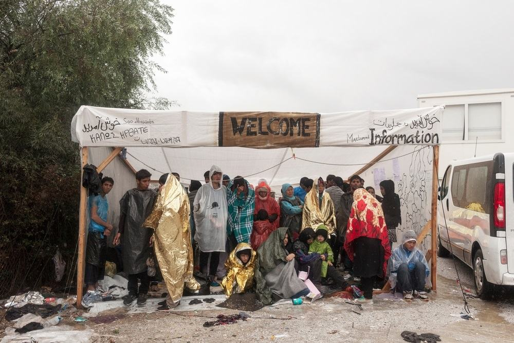 Photographer: Alessandro Penso<br/><br/>Caption: Refugees take shelter during a rain storm as they wait to be registered at the Moria Reception Centre in Lesbos, Greece.