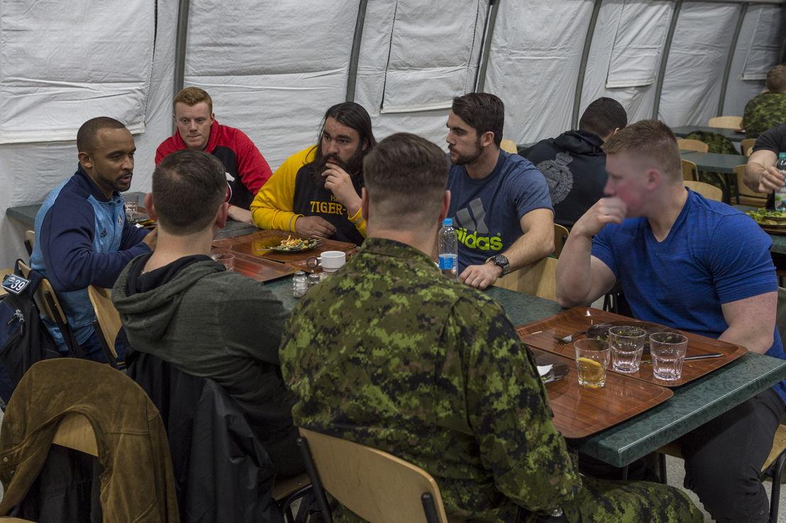 Matt Black (G), Andrew Buckley (C) et Mike Filer (D) discutent dans la mess avec des militaires déployés dans le cadre de l'opération UNIFIER à Starychi, en Ukraine. Photo : CplC Mathieu Gaudreault, Caméra de combat des Forces canadiennes