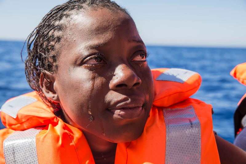 A woman from Ivory Coast cries after been rescued from a boat in distress on the Mediterranean. She was one of 435 people rescued from three separate boats on a single day in May by the MSF search and rescue ship Dignity I. Photographer: Anna Surinyach/MSF