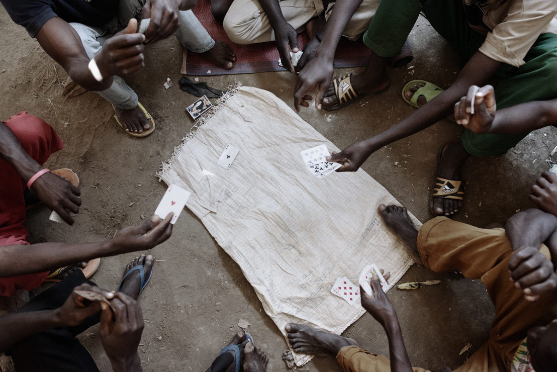 Refugees gather to play cards inside one of the mass shelters in Nyarugusu camp. The shelters were built to house 200 people, but in some cases, they host up to 370. Photographer: Luca Sola