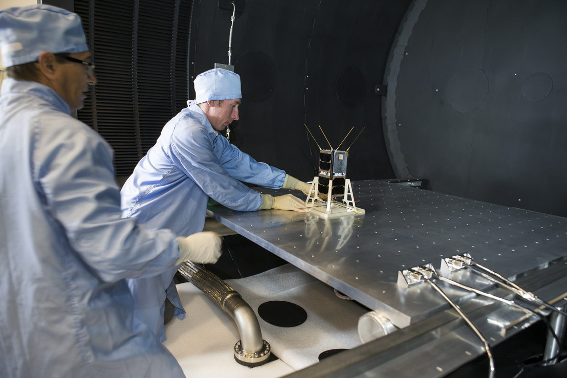 Mike Petrovic (L) and Bart Fordham from ANU load a CubeSat into the space simulator at the ANU Advanced Instrumentation and Technology Centre. Image: Stuart Hay, ANU.