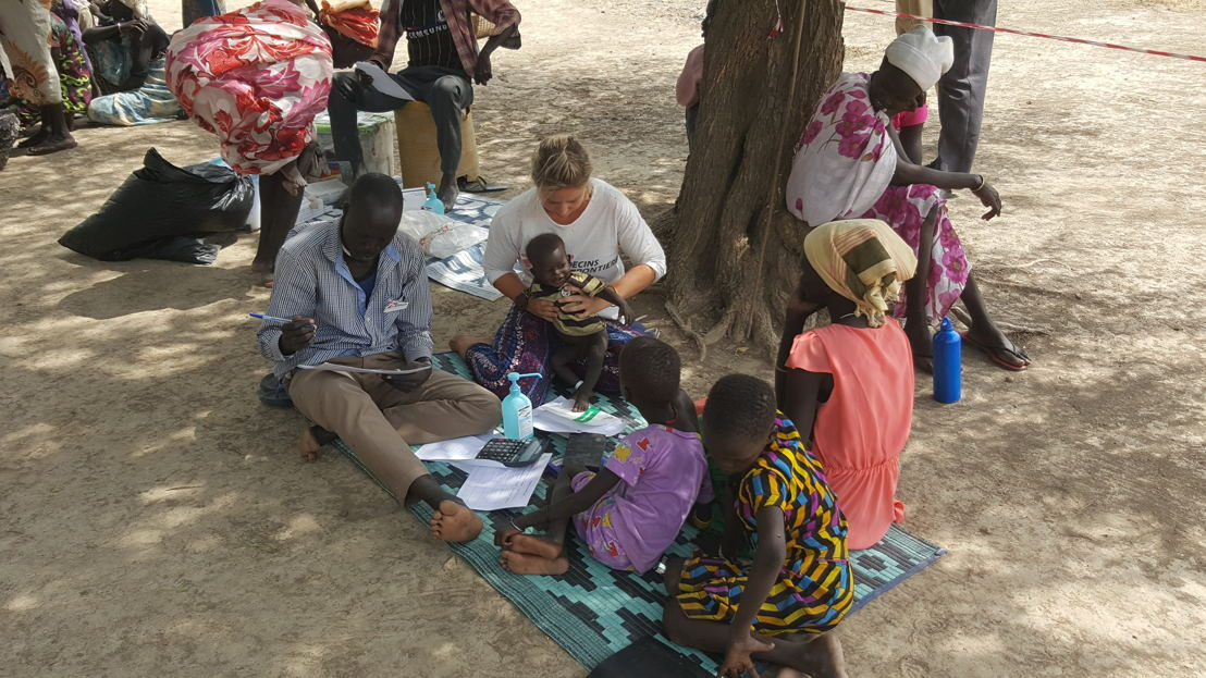 "Philippa Pett, ""Pippa"", MSF doctor from the UK and Richard, MSF Community health worker, are consulting a child suffering from malnutrition. Nicolas Peissel/MSF"