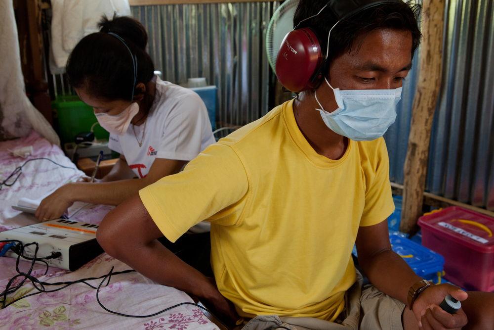 Thangkhoshin Hookip padece TB-MDR . Todos los días, las enfermeras de MSF lo visitan para administrarle una inyección y hacer seguimiento de la toma de los medicamentos diarios que necesita (15 pastillas). La enfermera realiza pruebas de audición dado que uno de las efectos secundarios de la medicación puede ser la pérdida completa de audición. © Jan-Joseph Stok.