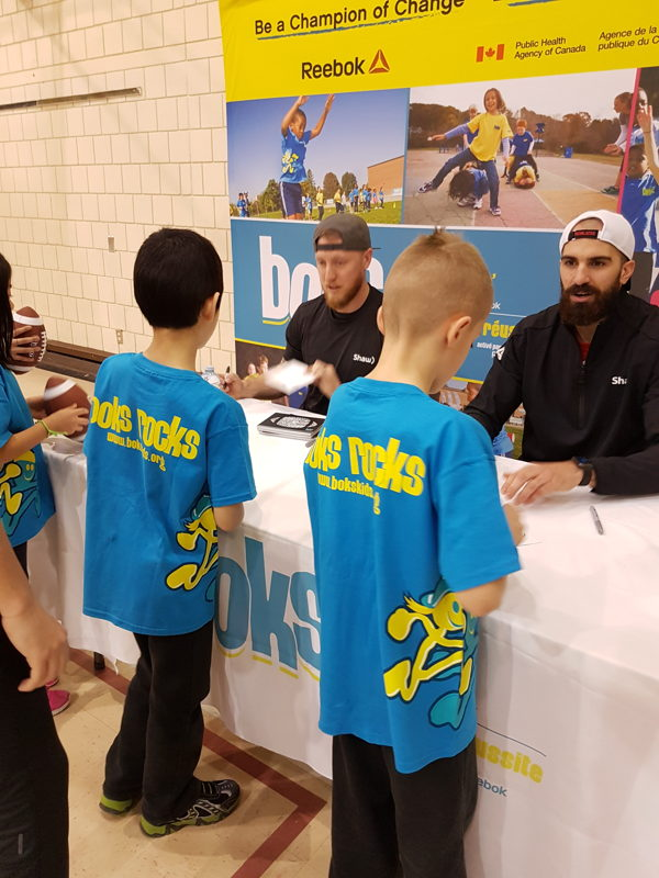 Bo Levi Mitchell and Brad Sinopoli signing autographs at Ecole Centennial Community School