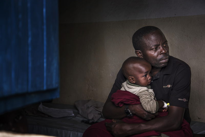 A father holds his son who is gradually recovering from cholera. Photographer: Arjun Claire