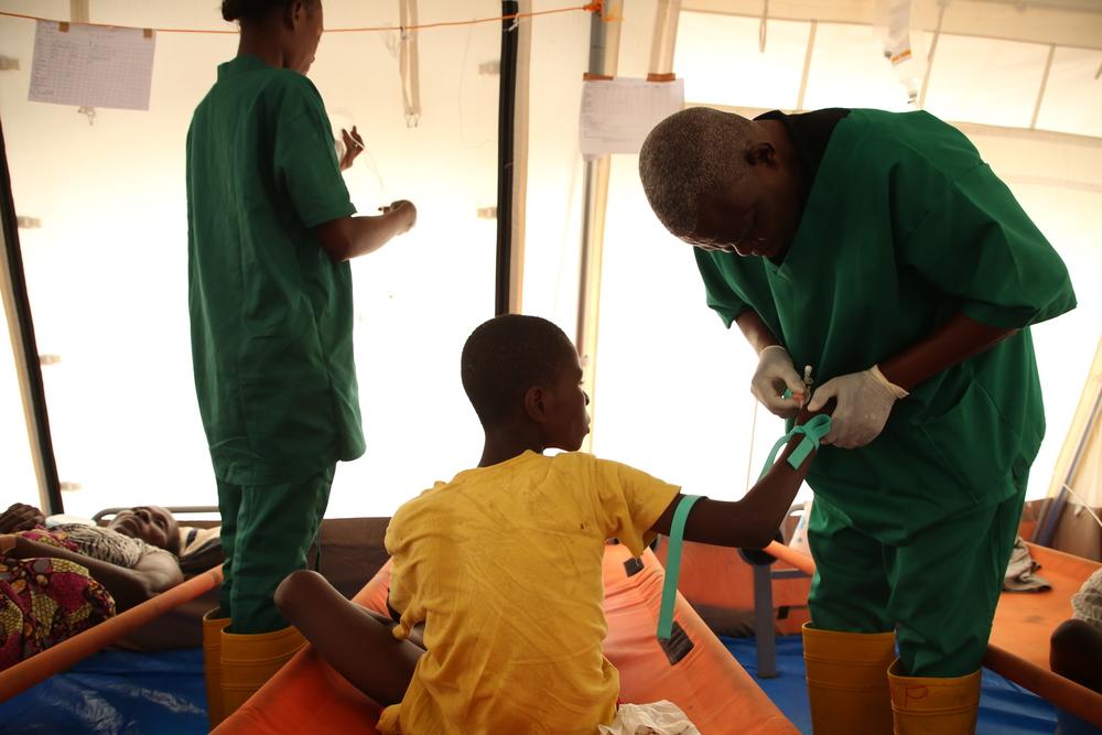 Een verpleger van Artsen Zonder Grenzen verzorgt een cholerapatiënt. © Carl Theunis/AZG