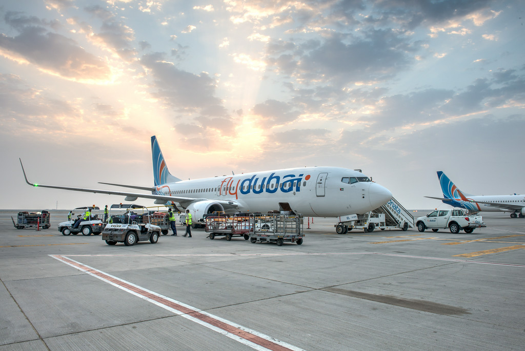 Aircraft on the ground surrounded by ground equipment and staff