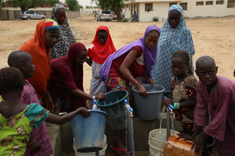 Nigerian women and children displaced by the conflict between Boko Haram and the Nigerian armed forces fetch water in the town of Banisheikh. Photographer: Igor Barbero