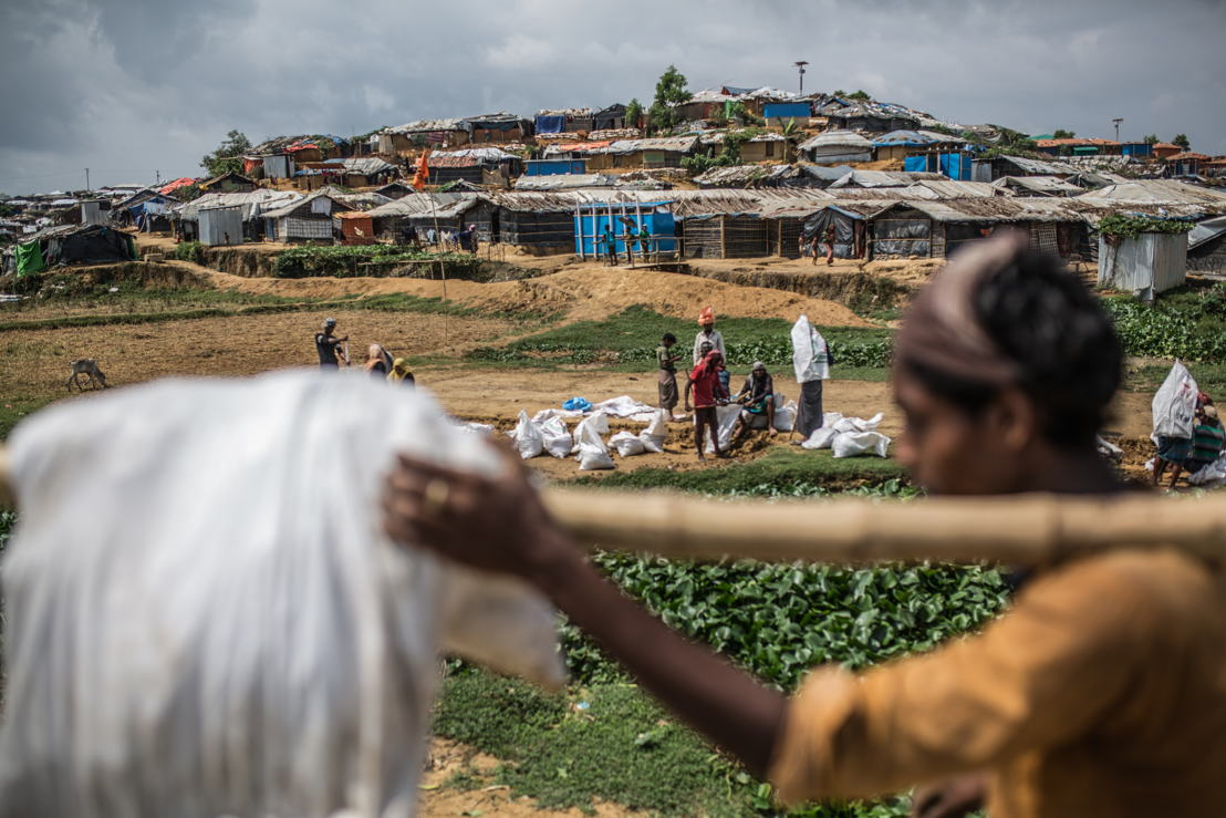 A group of refugees fill and transport bags of earth to strengthen the foundations of their fragile shelters, in preparation of the rains, winds and floods during the monsoon season. Photographer: Pablo Tosco