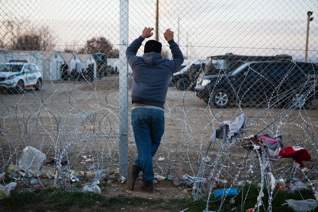 A man looks through the border fence into Macedonia (FYROM). Photographer: Alex Yallop