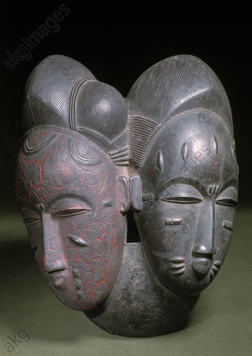 """Baule, Ivory Coast.<br/>Twin mask of the """"mblo"""" tribe.<br/>Wood painted red and black, height 29cm.<br/>Geneva, Collection Barbier-Mueller.<br/><br/>AKG582458"""