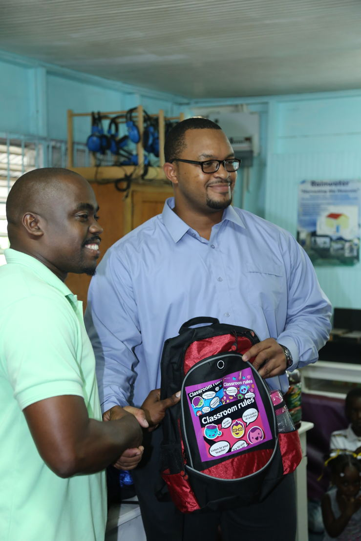Mr. Daniel Campbell, Intern from the CCRIF SPC within the OECS Commission, presents the donation of school supplies to Mr. Ezra Joseph, Principal of the Des Barras Combined School.