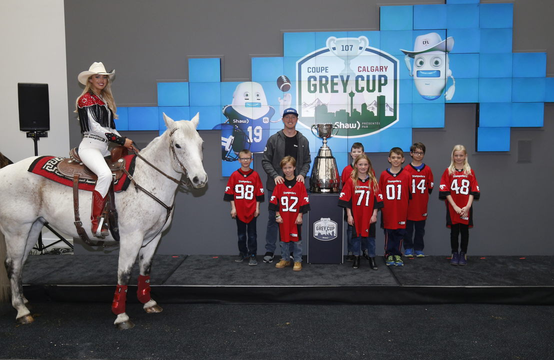 Chelsea Drake, Quick Six, and Stampeders quarterback Bo Levi Mitchell pose with the Grey Cup. Photo Credit: Todd Korol