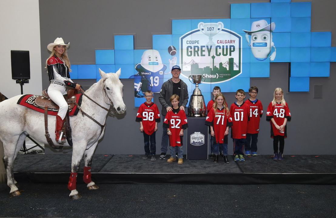 Chelsea Drake, Quick Six et le quart-arrière des Stampeders de Calgary Bo Levi Mitchell posent avec la Coupe Grey. Photo : Todd Korol/LCF.ca