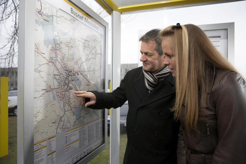 Reizigers raadplegen een netplan in een schuilhuisje van De Lijn<br/>Foto: Stefaan Van Hul