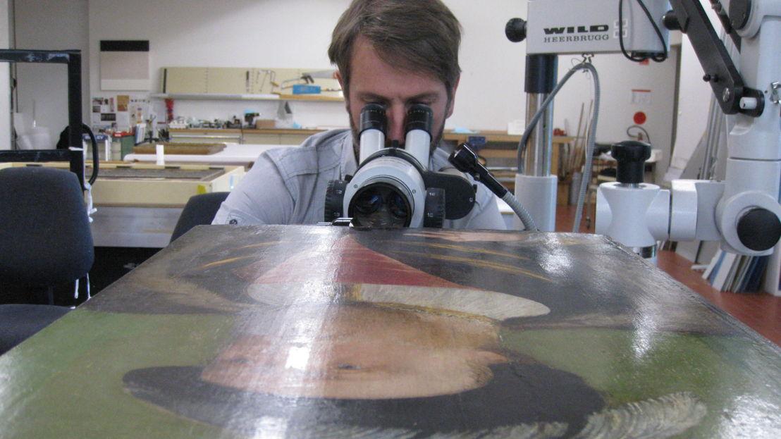 ANU academic, Dr Matthew Brookhouse examining the portrait. Image: Simon Ives