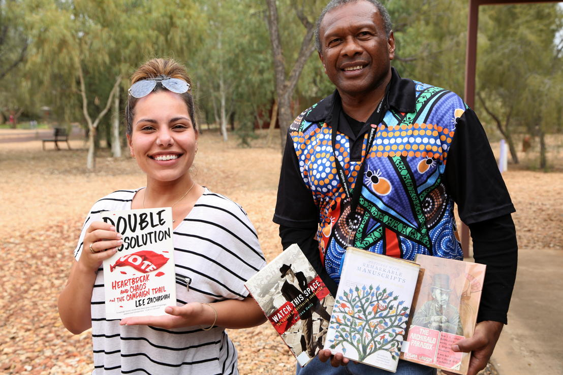 Batchelor Institute students Tiarne de Beer and Allen Minniecon in Alice Springs, with books donated by the ABC . Photo: Angela Harrison