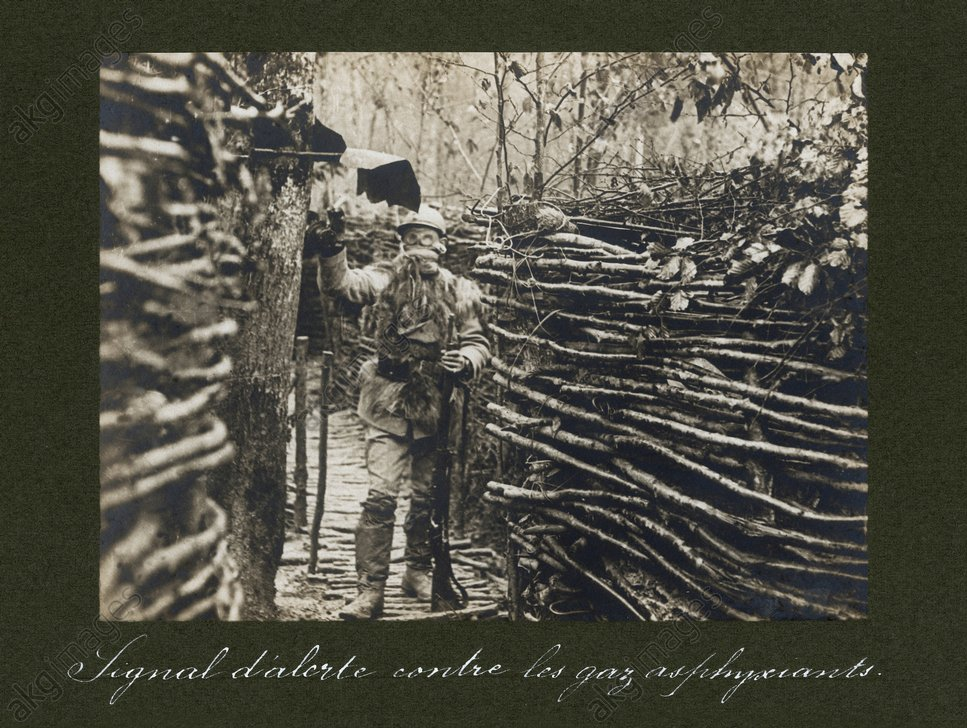 A French solider with a gas mask in the trenches next to a gas alarm.<br/>Photograph, undated, c. 1916<br/>AKG383273
