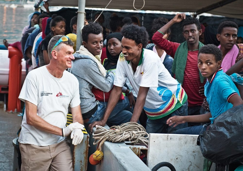 MSF doctor Pierre Vachaud shares a joke with a young man from Eritrea aboard an MSF search and rescue ship as the crew prepare to land on the coast of Italy. Photographer: Sara Creta