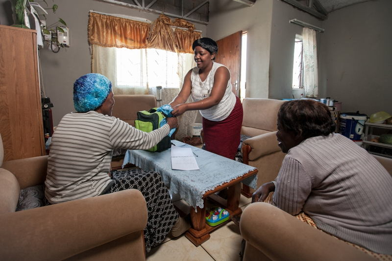 Community Care Giver Nonhlanhla Ngema delivers anti-retrovirals (ARVs) to Elizabeth, a member of her Community ART Group (CAG) in Sunnydale, Eshowe, KwaZulu-Natal. Medecins Sans Frontieres (MSF) has been piloting CAGs as a model of care for stable HIV+ patients in rural districts of southern Africa, where HIV prevalence is at its highest. CAG members meet once every two months to review their health and arrange for collection of their ARVs without having to sit in long queues at clinics. Photographer: Greg Lomas / Médecins Sans Frontières