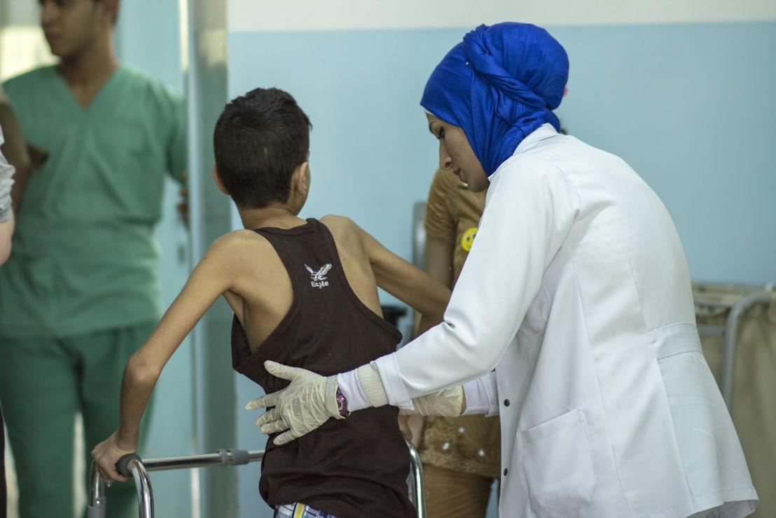 Fysiotherapeute Rula helpt het jongetje Fawzi overeind na zijn fysiotherapiesessie. Jordanië, Ramtha ziekenhuis, juni 2015.