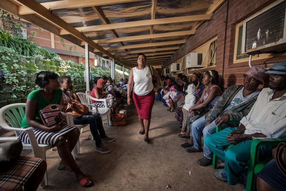 Community Care Giver Nonhlanhla Ngema passes a long queue of patients at Eshowe Gateway Clinic to pick up ARVs for members of her Community ART Group (CAG). Medecins Sans Frontieres (MSF) has been piloting CAGs as a model of care for stable HIV+ patients in rural districts of southern Africa, where HIV prevalence is at its highest. CAG members meet once every two months to review their health and arrange for collection of their ARVs without having to sit in long queues at clinics. Photographer: Greg Lomas / Médecins Sans Frontières