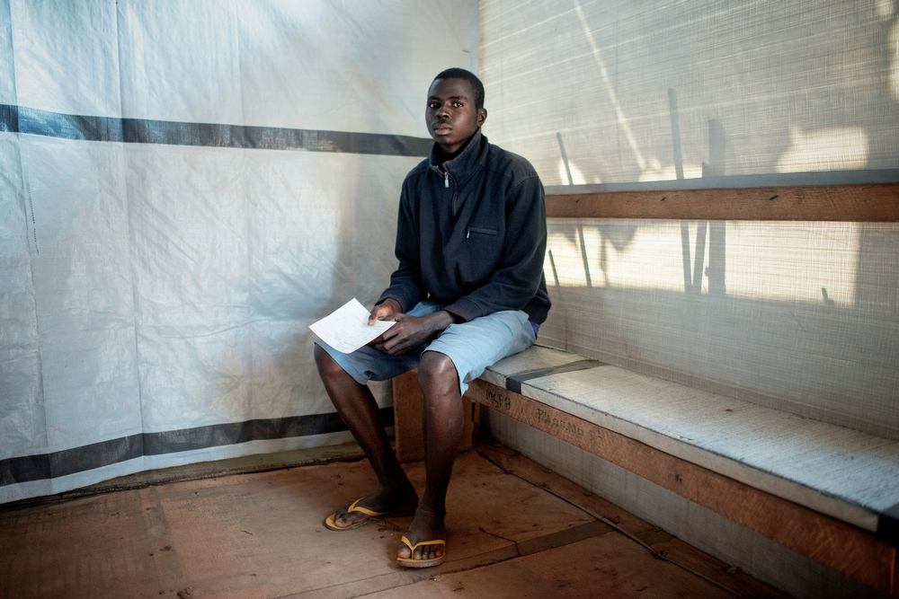 MSF159680<br/>20 year old Stéphane waits to be seen at a Medecins Sans Frontiers (MSF) hospital at a displaced persons camp in M&#039;Poko, Bangui.<br/><br/>&quot;When there is gunfire or grenades, I can not go to school&quot; says Stephane, who has lived in Mpoko Camp for two years. He had to flee his district, the 3rd arrondissement of Bangui, after a group of men burned his house and all the possessions of his family. Stéphane is a high school student and is the only person in his family that can earn money to support his five family members. Sometimes, he works as a daily worker at MSF's clinic in Mpoko.