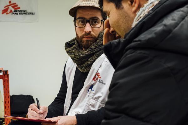 Un psychologue de MSF écoute un migrant afghan lors d'une consultation au Hub humanitaire de la gare du Nord en janvier 2018. (c) Bruno De Cock/MSF