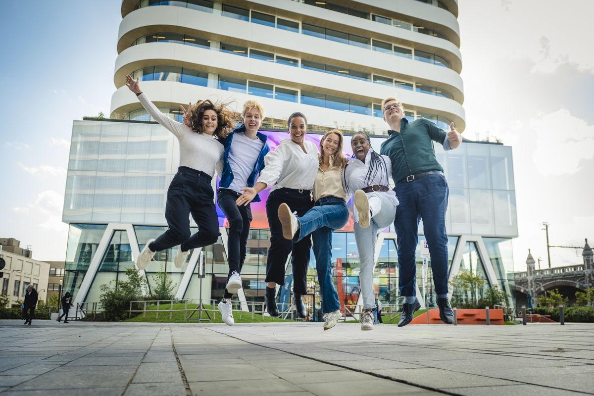 Glenn, Margo, Nikias, Ester, Rachel en Chloë voor het iconische gebouw van DPG Media in Antwerpen.