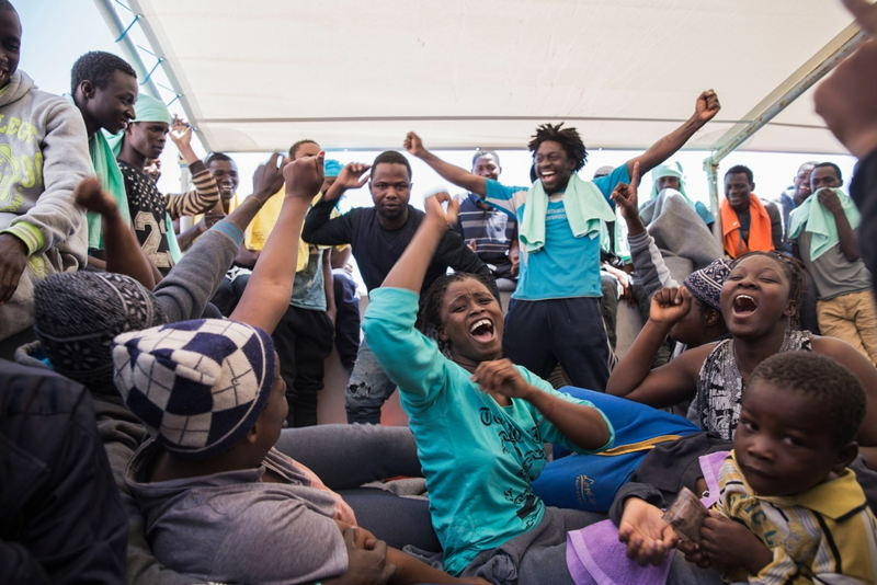 On board MSF's search and rescue ship Dignity I, people celebrate their rescue from a boat in distress. Some 435 people were rescued, most of them from Guinea, Mali, Ivory Coast and Senegal. Photographer: Anna Surinyach/MSF