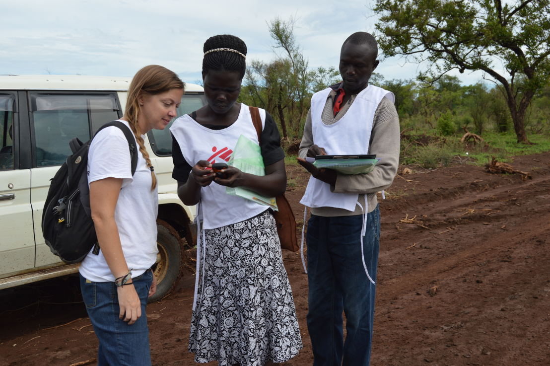 "MSF staff members pause on the road to look at the location of a sample household in Palorinya refugee settlement, northern Uganda. <br/>MSF runs a health surveillance system in Palorinya to monitor and detect changes within the population and to help inform its medical and humanitarian interventions. <br/>Quotes from Sam Hoare, a public health physician who recently returned from Uganda where he was working on an emergency health surveillance system in Palorinya: ""We also use the information and data to advocate for more services from other organisations that can support the refugee population with things like latrines or hand washing facilities.<br/>The team collects information about births, deaths and ill health from individuals through weekly household interviews, while also collecting medical data from health facilities in and around the settlement. Household interviews are a really important part of our data collection work, as we can build a better understanding of peoples lived experiences and needs, rather than only being exposed to those who are able to visit health facilities. <br/>In acute emergencies like this, when large communities are in chaotic new environments and new countries, it can be very difficult to understand their health status, making the population particularly susceptible to epidemics and diseases. Outbreaks of infectious diseases are common; in addition, the rainy season increases outbreaks of diseases like malaria, and often hinders access to health services. A functioning health surveillance system helps us detect changes in the health of the population, meaning we can respond to identified needs.<br/>We have trained a team of over 100 surveillance officers from within the refugee settlement in the hope that they are more familiar with local customs, language and culture, and can collect more accurate information on sensitive topics such as deaths. We use this data to inform medical activities, and project trends such as birth and death rates across. Photographer: Yuno Cho"