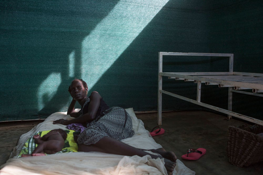 Nyakuech Mach, 30 lies on a bed in the prenatal ward of the Kule health center in the Kule refugee camp in the Gambella region of Ethiopia on 25 Oct 2017. She gave birth to a boy, Doctor Nyak, premature, 7 days earlier. Photographer: ZACHARIAS ABUBEKER