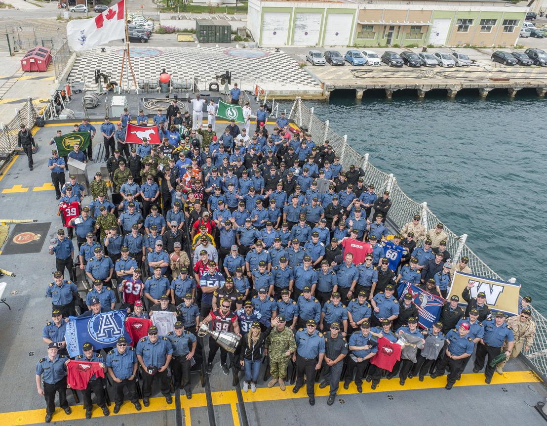 Des joueurs de la LCF et des membres des Forces canadiennes à bord du NCSM St-John's à Marseille, en France.