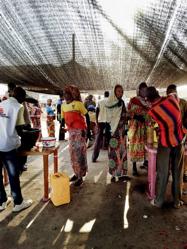 Women stand in line to receive donations of rice, beans,oil, salt and sugar from MSF teams. Photographer: MSF