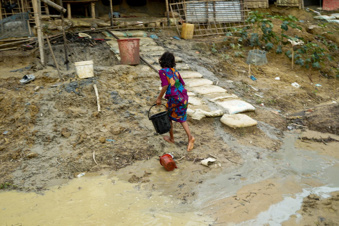 A Rohingya girl carries a bucket of water back to her tent dwelling in Balukhali camp, just before a heavy downpour. Whenever it rains, many parts of the camps become flooded, and some tents collapse or are swept away by rains or landslides. When it rains, tap stands can become infected with dirty water, and some latrines collapse, posing a risk to people's health. One year on since the biggest influx of Rohingya refugees to Bangladesh, watery dirrhoea remains one of the main morbidities treated by MSF teams. Photographer: Dalila Mahdawi